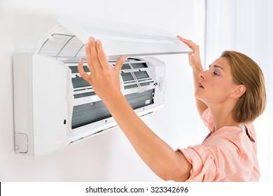 家でエアコンを開ける若い美人