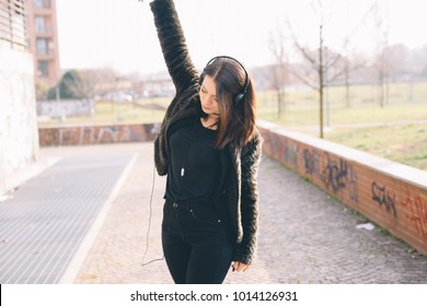 young beautiful woman outdoor listening music - relaxing, dancing, music concept