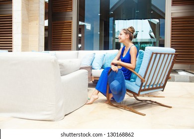 Young beautiful woman outdoors sitting in hotel lobby, bali
