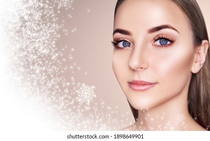 Young beautiful woman over beige background with snow and snowflakes. Cryolifting concept.