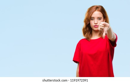 Young beautiful woman over isolated background looking unhappy and angry showing rejection and negative with thumbs down gesture. Bad expression.