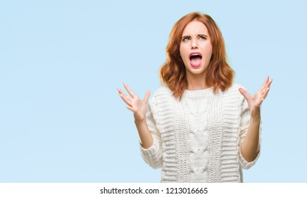 Young beautiful woman over isolated background wearing winter sweater crazy and mad shouting and yelling with aggressive expression and arms raised. Frustration concept.