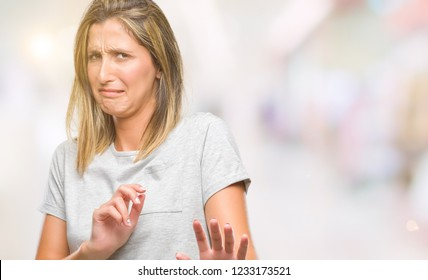 Young beautiful woman over isolated background disgusted expression, displeased and fearful doing disgust face because aversion reaction. With hands raised. Annoying concept.