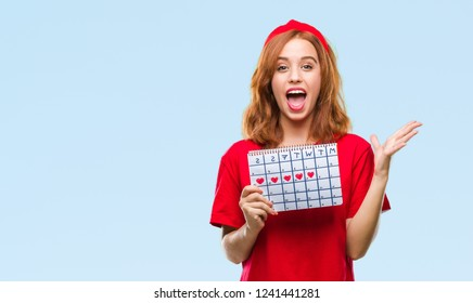 Young beautiful woman over isolated background holding menstruation calendar very happy and excited, winner expression celebrating victory screaming with big smile and raised hands