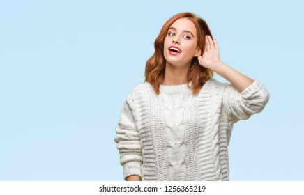 Young beautiful woman over isolated background wearing winter sweater smiling with hand over ear listening an hearing to rumor or gossip. Deafness concept.