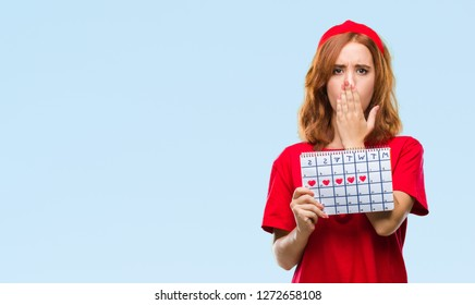 Young beautiful woman over isolated background holding menstruation calendar cover mouth with hand shocked with shame for mistake, expression of fear, scared in silence, secret concept
