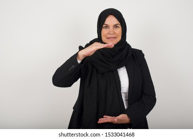 Young beautiful woman over isolated background gesturing with hands showing big and large size sign, measure symbol. Smiling looking at the camera. Measuring concept.