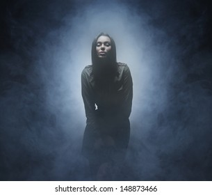 Young and beautiful woman over the smoky background