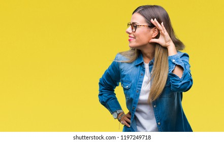 Young beautiful woman over wearing glasses over isolated background smiling with hand over ear listening an hearing to rumor or gossip. Deafness concept.