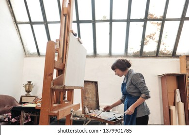 Young beautiful woman painter among easels and canvases in a bright studio. Inspiration and hobby.