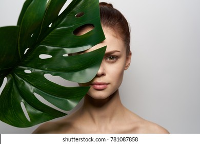 young beautiful woman with a palm leaf, clean skin