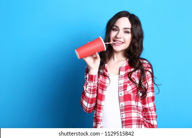 Young beautiful woman with paper cup on blue background