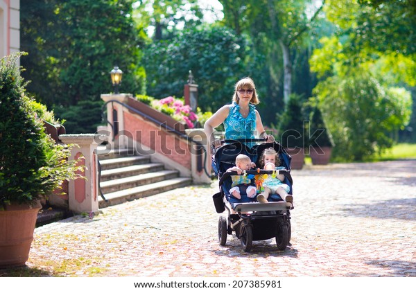 Young beautiful woman in a park with a double jogging stroller with two kids, baby boy and little toddler girl, brother and sister, walking fit and active on a hot summer day