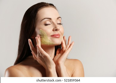 Young beautiful woman with peeling scrub on face on grey background