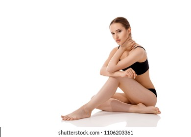 young beautiful woman with perfect body in black underwear sitting on floor isolated on white background