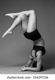 Young beautiful woman performing headstand against gray background, black and white