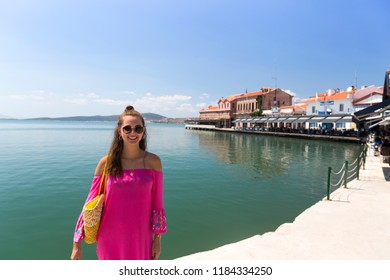 Young Beautiful Woman in Pink Dress standing in front of Old harbour view in Ayvalik Center. Ayvalik is popular tourist destination in Balikesir, Turkey.