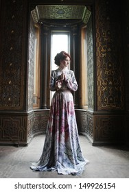 young beautiful woman in pink dress posing in luxury palace