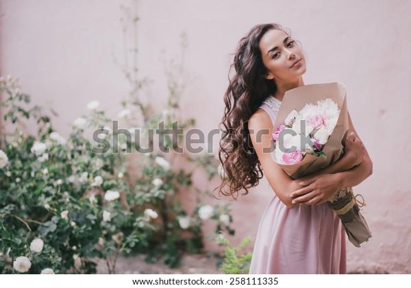 バラの庭で牡丹の花束をポーズにしたピンクのドレスを着た若い美しい女性