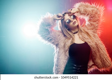 Young beautiful woman in pink fur coat. Background of smoke and neon light