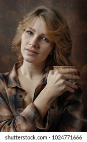 Young beautiful woman in plaid shirt with coffee mug . Beautiful blondel on brown background.