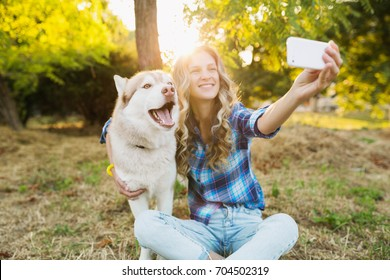 young beautiful woman playing with dog in park, summer lifestyle, casual style, sunny, smiling, happy, positive, husky breed, making selfie photo on smartphone, backlight