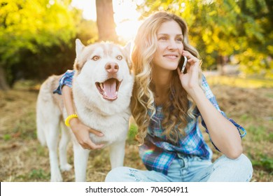 young beautiful woman playing with dog in park, summer lifestyle, casual style, sunny, smiling, happy, positive, husky breed, talking on phone, backlight