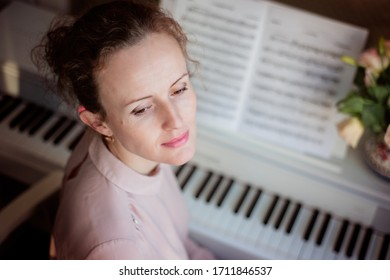 Young beautiful woman is playing piano at home. Music concept