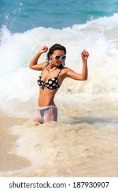 Young Beautiful Woman playing in waves on beach
