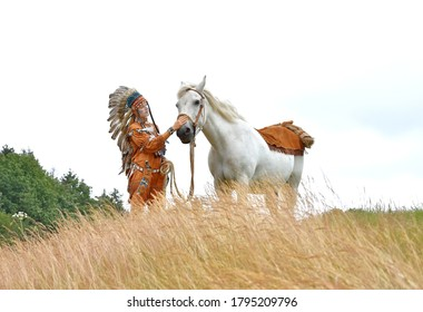 A young beautiful woman plays the part of a native American  Indian. She is seen in a meadow tending to her white stallion.