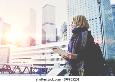 Young beautiful woman with portable touch pad in hands is enjoying view of New York business center outside the window background with copy space for advertising text message or promotional content