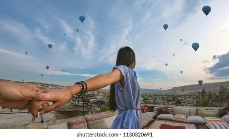 Young beautiful woman portrait in front of Cappadocia landscape at sunshine with balloons in the air. Turkey.