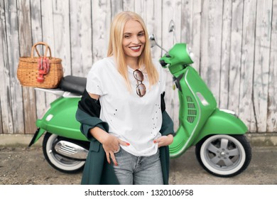 A young and beautiful woman poses for a photographer next to a scooter.