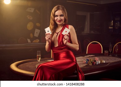 Young beautiful woman is posing against a poker table in luxury casino.