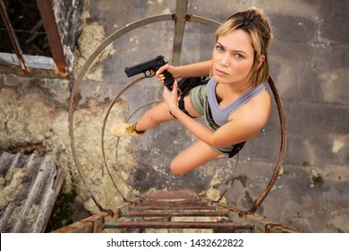 Young beautiful woman posing in airsoft game photoshooting set