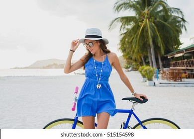 young beautiful woman posing with bicycle on beach, blue boho dress, hipster style, hat, sunglasses, skinny body, smiling, happy, positive mood, tropical vacation, summer fashion