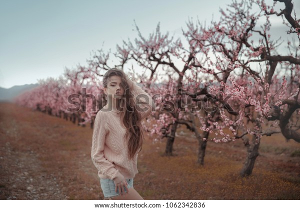 Young beautiful woman posing by the blossom spring tree. Outdoor photo of pretty brunette girl with healthy long curly hair over pink peach blossom garden.
