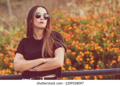Young beautiful woman posing in flowers field with crossed arms