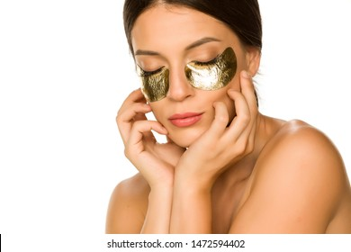 Young beautiful woman posing with golden patches under her eyes on white background