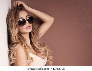 Young beautiful woman posing in mini dress. Studio shot. Long curly hair. Glamour makeup.