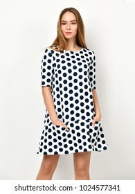 Young beautiful woman posing in new casual black and white dotted dress on a white background