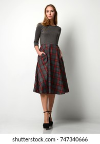 Young beautiful woman posing in new fashion plaid skirt and gray full body on a white background
