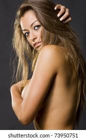 young beautiful woman posing nude in a photo shooting in the studio