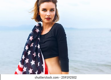 Young beautiful woman posing at sea side, holding american flag, wearing crop top and gothic bright make up. Rainy day, foggy weather.