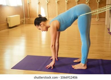 young and beautiful woman practicing yoga kurunta. stretching the arms, back and spine ( yoga kurunta )