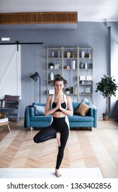 Young beautiful woman practicing yoga, tree pose in living room at home. Balance and meditation.