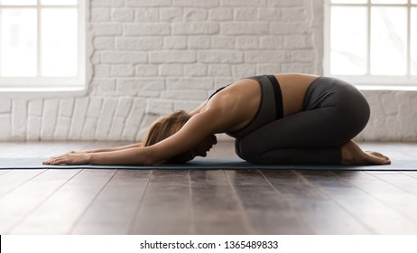 Young beautiful woman practicing yoga, lying in Child pose, Balasana exercise, attractive girl in grey sportswear, leggings and bra working out at home or in modern yoga studio with white walls