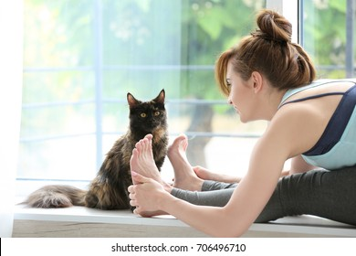 Young beautiful woman practicing yoga pose and cat on windowsill