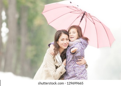 Young beautiful woman with pretty little daughter in park under umbrella. Mother and daughter together. Friendly family being happy and cheerful. Family outdoor in rain.
