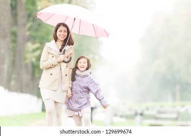 Young beautiful woman with pretty little daughter walking together in park under umbrella. Mother and daughter holding hands. Friendly family being happy and cheerful. Family walk outdoor in rain.